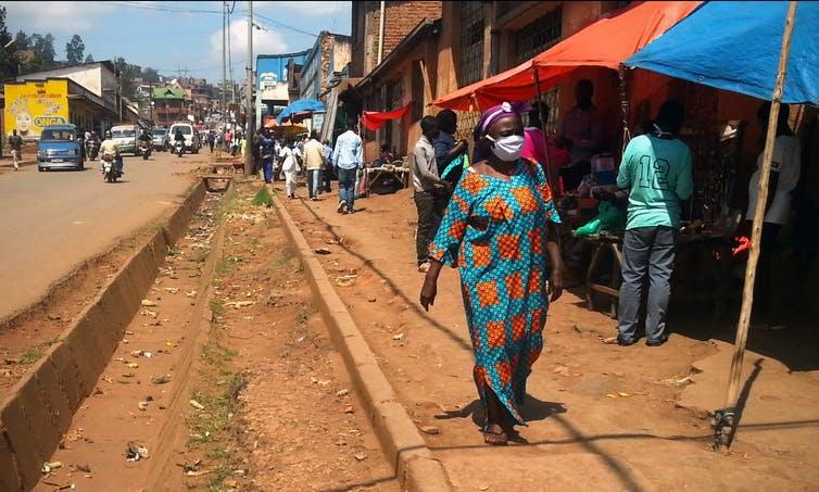 Femme se promenant masquée dans les rues de Bukavu, avec des passants en arrière-plan.