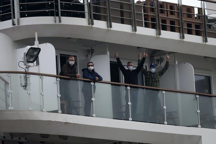 Quatre passagers masqués font signe depuis un balcon, à bord du bateau de croisière Greg Mortimer.