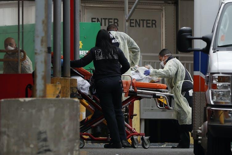 Des soignants transportent un patient sur un brancard, dans un hôpital de New York.
