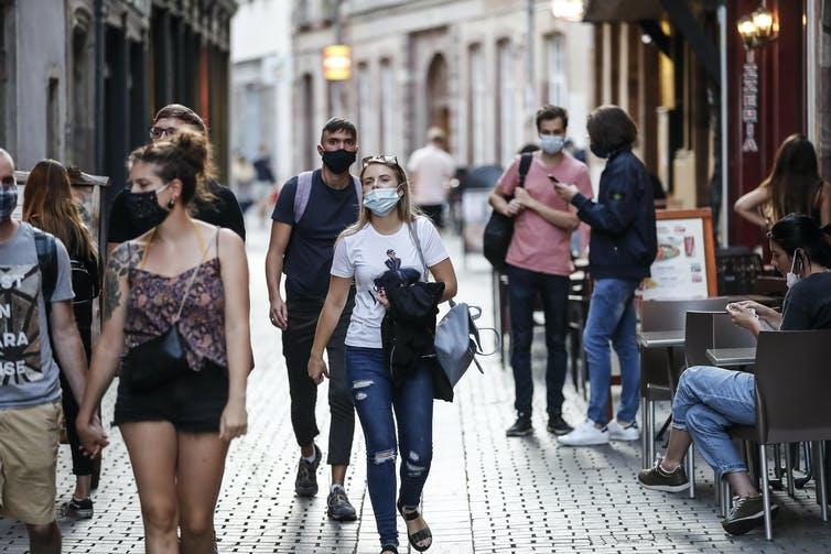 Des jeunes portant des masques dans une rue pavée.
