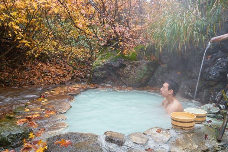 Un homme est assis dans une piscine d'eau chaude laiteuse sous un feuillage d'automne.