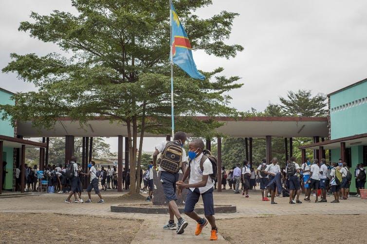 Des élèves masqués jouent dans une cour d'école à Kinshasa.
