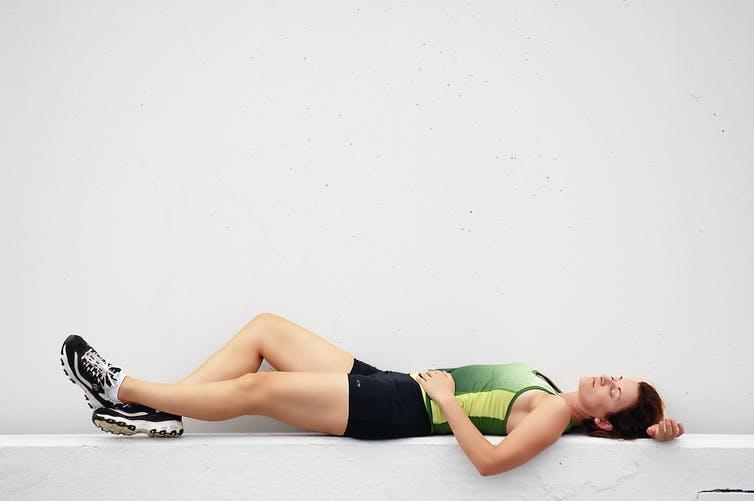 Femme en tenue de sport dormant sur un banc de béton
