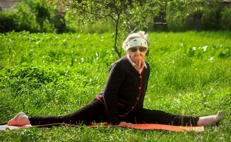 Photo d'une femme très âgée qui fait un grand écart dans son jardin, sur un tapis de sol.