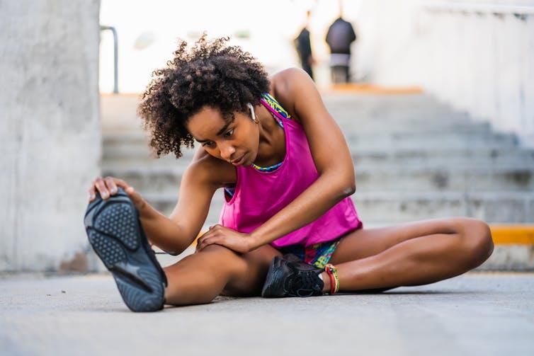 Jeune femme en tenue de sport pratiquant des étirements assise sur le sol, au pied d'un escalier.