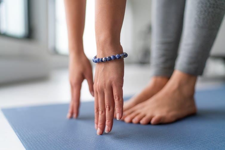 Gros plan d'une personne touchant le sol devant ses pieds avec le bout de ses doigts.