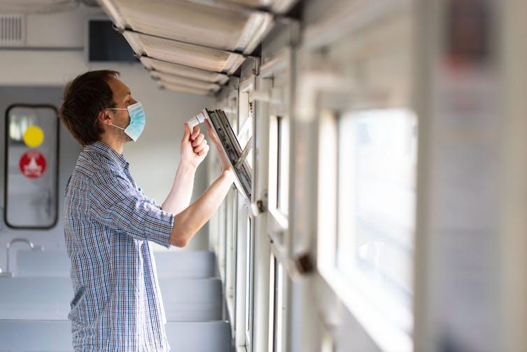 Un homme ouvre la fenêtre dans un train pour permettre d'aérer